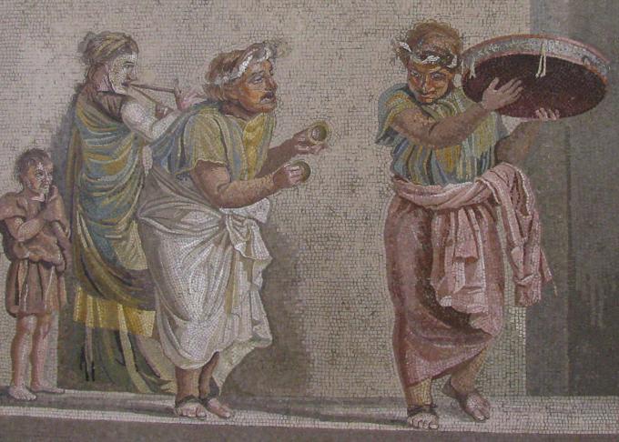 mosaico romano com cena de comédia. atores mascarados dançam ao som de percussão & sopro.